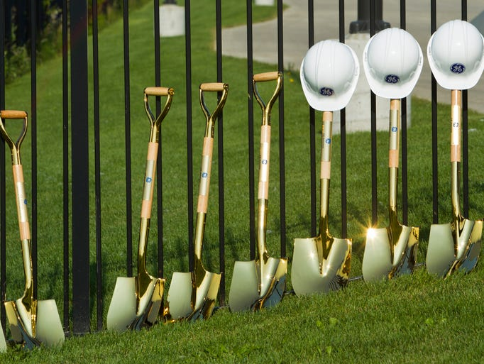 Helmets and shovels line a fence before a groundbreaking ceremony for a General Electric Aviation facility Monday, July 21, 2014, in Lafayette. The plant will build  GE's LEAP jet engine, a high-efficiency aircraft engine . The plant is expected to employ 200 people.