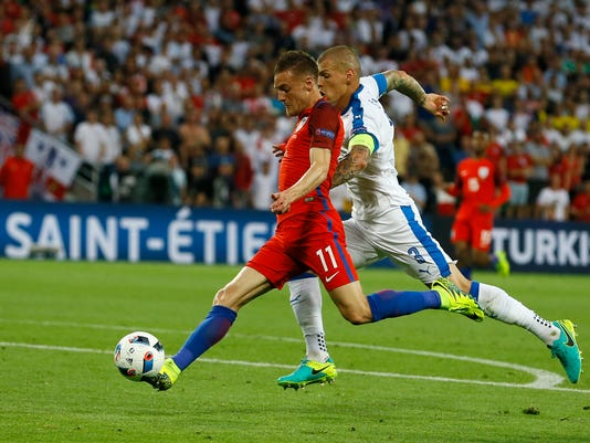 England's Jamie Vardy, left, attempts a shot at goal while chased by Slovakia's Martin Skrtel during the Euro 2016 Group B soccer match between Slovakia and England at the Geoffroy Guichard stadium in Saint-Etienne, France, Monday, June 20, 2016. (AP Photo/Kirsty Wigglesworth)