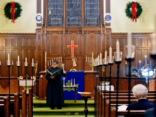 The Rev. Beth Schlegel holds a lighted candle as she leads St. Peter's Lutheran Church's Blue Christmas Service of Healing and Peace Thursday, Dec. 21, 2017, in North York. Held on or near Dec. 21, the longest night of the year, to recognize the various struggles people face during the holiday season, Blue Christmas services are increasingly common.