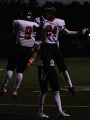 Omar Morris (9) celebrates his second of three touchdowns Friday night with teammate Jake Mushinski.
