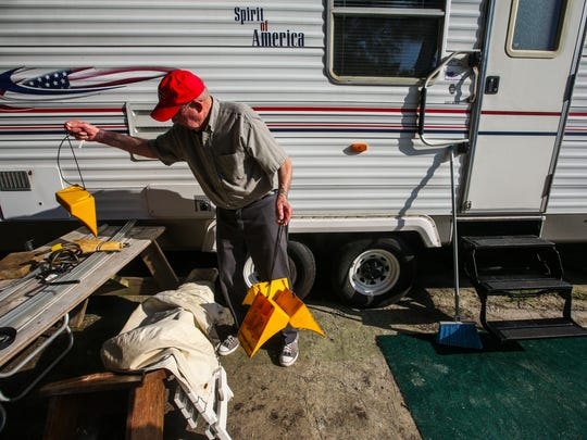 Waylon organizes the tire stops after he pulled them from the wheels on the trailer before they pulled away. Waylon and Barbara Snead have spent the entire month of March at Sanibel's Periwinkle Park campground for the past 19 years. They departed with their travel trailer Friday morning, for their home in Raleigh North Carolina. They spent Friday morning packing up the last few things into the back of their pickup truck and trailer for the four-day journey. They will stop and visit friends and family along the way home. Shot on April 1, 2016.