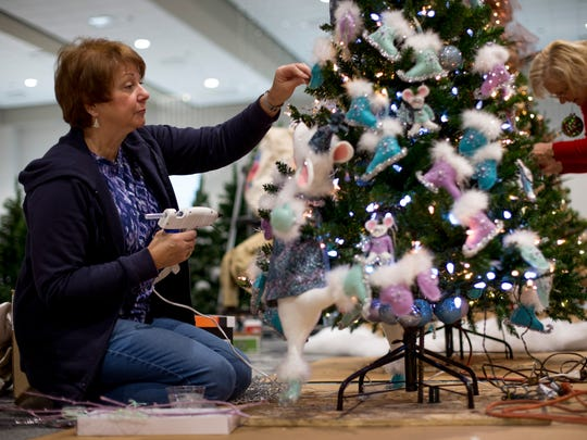 Patricia Toth, of Clyde Township, sets up a tree in