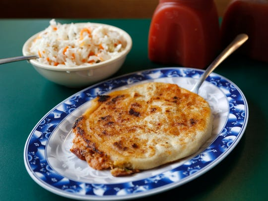 A pork pupusa (center) is served with a cabbage salad