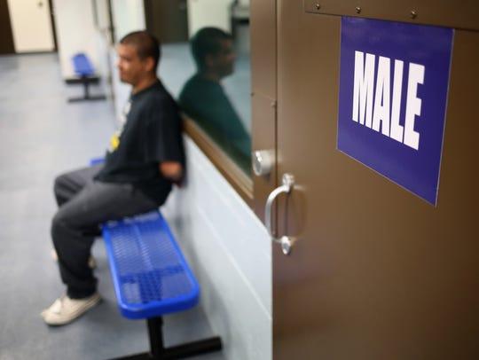 Un hombre espera para ser procesado en una instalación