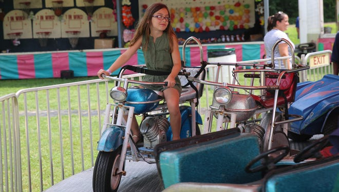 Kinley Kemnitz, 9, rides on a motorcyle on a carousel ride on Saturday at Pleasant Valley Weekend. Her mother grew up going to the event.