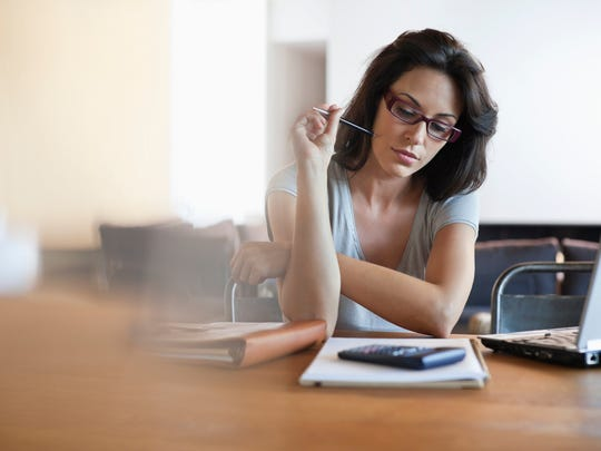 Woman thinking while looking at laptop and notepad.