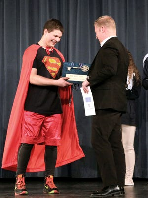 Mayor Justin Nickels (right, one of the Mr. Roncalli judges) presents winner Simeon Newton with a key to the city.
