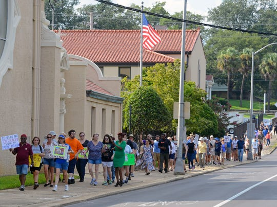 Ralliers make their way down Palafox St. Sunday, August 13, 2017 during the Love is Louder-Stand with Charlottesville walk to support peace in Charlottesville. More than 100 people made their way up Palafox in silence carrying signs to stop racism and promote peace.