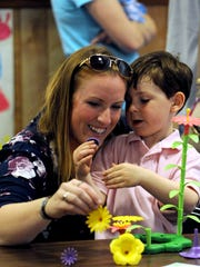 Wayton Cordle, 4, shows his mother Alicia Cordle a plastic flower blossom as they play together during a flower shop experience at Redeemer Lutheran Church and Child Care in Lancaster. The child care hosted a flower shop event for their mothers and grandmothers.