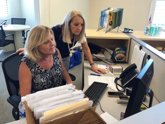 Mary Quinton and Linda Flores look over some work in the new Marco Eagle office.