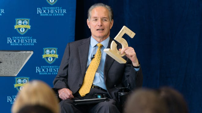 Dr. Bradford Berk, senior vice president and CEO of the University of Rochester Medical Center, holds up a wooden number 5, made by his assistant, to mark the anniversary of the spinal cord injury suffered in a bicycle accident. Berk announced Wednesday he will give up the CEO position at the end of the year to start the Rochester Neurorestorative Institute.