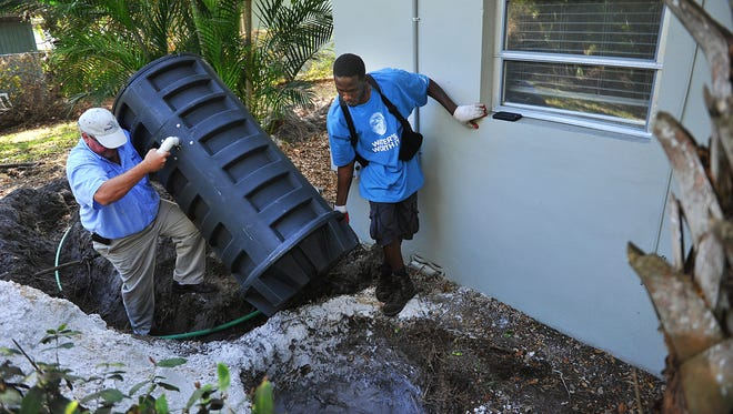 Cornelius Kossen (left) of the Stuart Public Works Department and Holwinster Alexis install a grinder tank in 2015 at a home on Osceola Street in Stuart. The system, which could be used if neighborhoods in northern Sewall's Point vote to switch from septic tanks to the Martin County sewer system, grinds sewage which is pumped through a 1.25-inch hose also buried in the yard into an established sewer line.