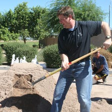 With Vice Mayor Jim Waring helping, Phoenix Mayor Greg Stanton demonstrates how to fill a sandbag Monday.