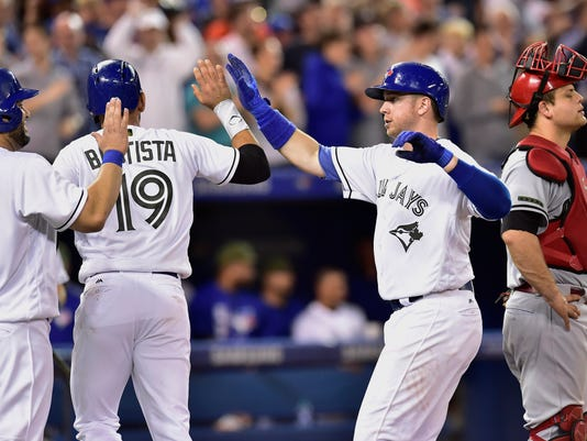 Toronto Blue Jays designated hitter Kendrys Morales, from left, and Jose Bautista (19) celebrate with Justin Smoak after Smoak hit a three-run home run as Cincinnati Reds catcher Devin Mesoraco (39) looks on during the fourth inning of an interleague baseball game in Toronto on Monday, May 29, 2017. (Frank Gunn/The Canadian Press via AP)