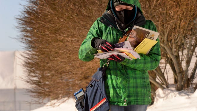 Christine Brockmann delivers mail Thursday to homes off of 16th Street in Two Rivers on a bitterly cold day.
