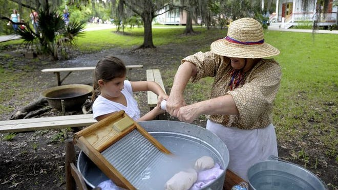 Adrian Edmond, 7, learns how to hand-wash clothes from Earlene Broussard during a demonstration for Acadian Culture Day at Vermilionville in Lafayette, La., Sunday, Aug. 3, 2014.
