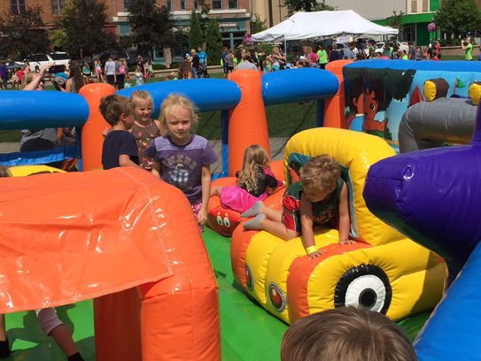 Children play in a bounce house at Family Fitness Fest