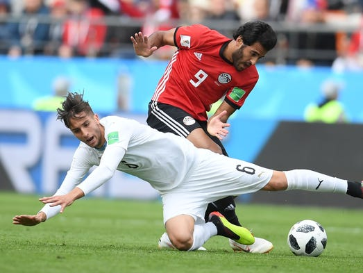 Egypt's Marwan Mohsen vies for the ball with Uruguay