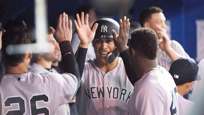 Giancarlo Stanton celebrates with his teammates.