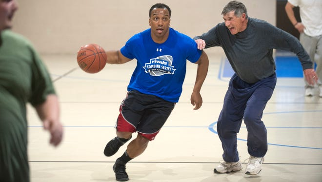 Glassboro Police Officer Craig Rawles drives to the basket as he is closely guarded by Glassboro resident and Calvary Hill Church member Bob Black during a pickup basketball game at Calvary Hill Church in Glassboro on Monday.  Members of the Glassboro Police started a department basketball team to connect with the community.