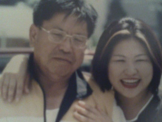 An old photo of Choi Eun-suk posing with her father, now deceased, who was born in North Korea and fought with Americans during the Korean War.