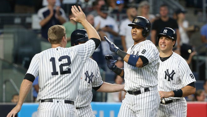 New York Yankees' Starlin Castro, second from right, is greeted by teammates Mark Teixeira, right, Chase Headley, left, and Brian McCann after hitting a grand slam during the third inning of the baseball game against the Cleveland Indians at Yankee Stadium, Friday, Aug. 5, 2016 in New York.