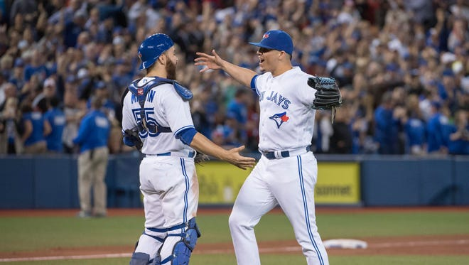 Blue Jays closer Roberto Osuna celebrates the win with Russell Martin at the end of the game.