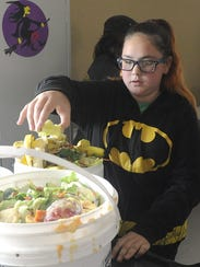 Eighth-grader Lily Calvet puts an apple core in a compost