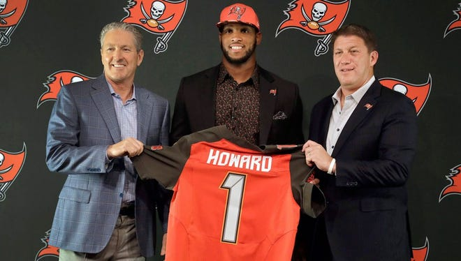 Tampa Bay Buccaneers 2017 first round draft pick O.J. Howard, center, holds a jersey as he poses with head coach Dirk Koetter, left, and general manager Jason Licht.