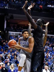 University of Memphis forward Dedric Lawson (left) drives the lane against University of Central Florida defender  Tacko Fall (right) during second half action at the FedExForum.