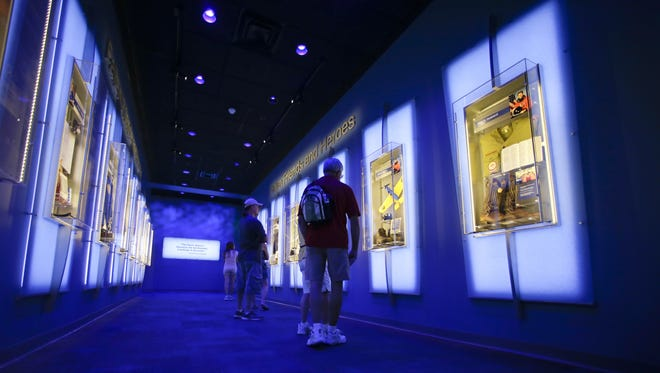 """In this Tuesday, July 21, 2015 photo, visitors look over display cases at the """"Forever Remembered"""" exhibit and memorial for the astronauts that perished on the Columbia and Challenger space shuttles, at the Kennedy Space Center Visitor Complex in Cape Canaveral, Fla. NASA's intent is to show how the astronauts lived, rather than how they died."""