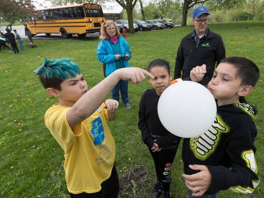 Fernwood Montessori School students and teacher Tillie Sullivan (back left) participate in an Urban Ecology Center outdoor science class at Washington Park.