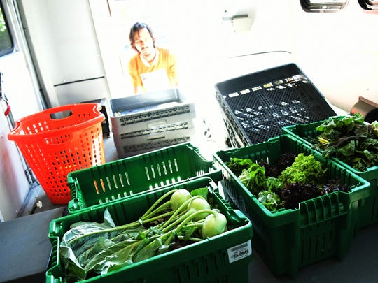 Fresh Food Farms assistant manager Erick Negron loads fresh greens into the mobile van after a press conference for the Fresh Food Farms Mobile Produce Market at the Rabbit Transit transfer station in York City Friday, June 15, 2018. The mobile market will make regularly scheduled stops at eight city locations to offer fresh produce affordably. The farm grows its produce at two York City locations. Bill Kalina photo