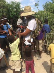 Ragin' Cajuns starting quarterback Brooks Haack is surrounded by young Haitian children during a recent mission trip to the country.