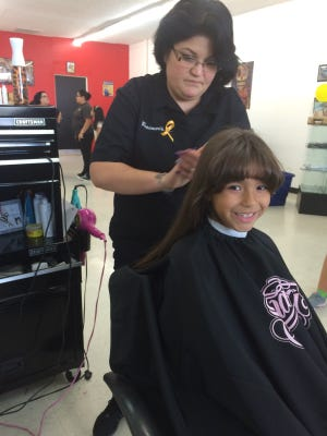 Hair Mechanix co-owner Rosemarie Fernandez cuts Bella Apodaca's hair Saturday at 4950 Hondo Pass, Suite E, in Northeast El Paso.