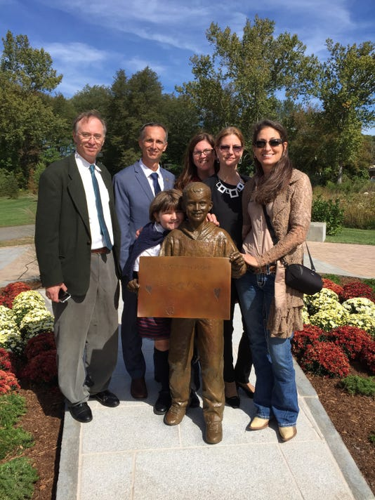 The Richard family and three artists pose with sculpture