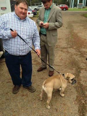 Patrick Jeansonne (left) holds Jethro, his 5-year-old English bulldog, on his leash Monday in Marksville. Jeansonne and his attorney, Aaron Broussard of Lake Charles, sued Marksville police Lt. Derrick Stafford and the city over Jeansonne's arrest in July 2013 as he was trying to get the dog, which was seriously ill with a heatstroke, to a vet's office.