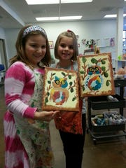 Talia Mesecar and Naomi Hamlin show their art they made at Young at Art.