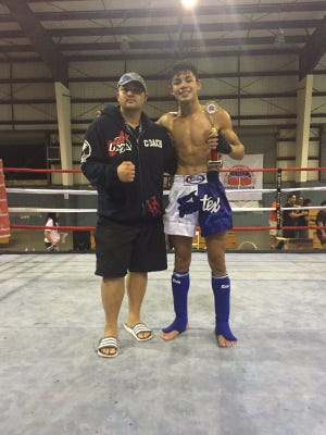 UMA head coach Henry Herr, left, and fighter Ethan Reyes celebrate after Reyes beat Robert Wusstig (not pictured) by unanimous decision to win the main event during a kickboxing fight at the Yigo gym in December, 2015.