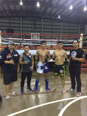 Ethan Reyes, 17, center, is joined by, from left, coach Henry Herr, pro fighter Josh Alvarez, Robert Wusstig and UFC fighter Jon Tuck after Reyes beat Wusstig to win the main event during a kickboxing fight at the Yigo gym in December, 2015.