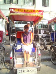 Yvonne sits in a cyclo, Hanoi's fun transportation, a seat for one person or two mounted over two wheels of three and powered by a bicyclist.