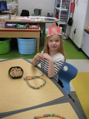 Madeline Hanson makes a necklace out of 100 fruit loops.