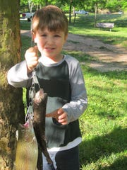 Berney Hale, 5, Harrison Ark., with a rainbow trout he caught during Kid's Free Fishing Day at Bennett Spring.