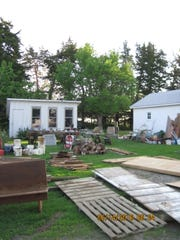 The accumulated agricultural debris of 40 years of rural Iowa life sits in the barnyard, waiting to be auctioned off.