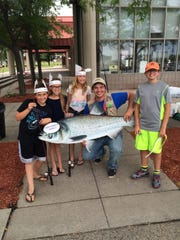Milliken State Park explorer guide Troy Linton, with his nieces and nephews, pose with an Asian Carp cutout during a fishing program and discussion about aquatic invasive species.