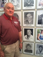 Marshall Goss, director of the Indiana Track and Cross Country Hall of Fame, with his induction picture. Goss is the former coach at Bloomington South and IU.