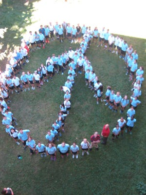 Mater Christi School staff, teachers and students from grades six, seven and eight forming an immense peace sign on the school lawn. Photo was taken from the top floor of the MCS middle school building.