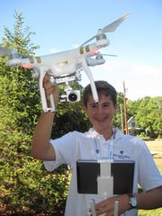 Alexander Preis of Shelburne, an eighth-grader, posing with his drone.