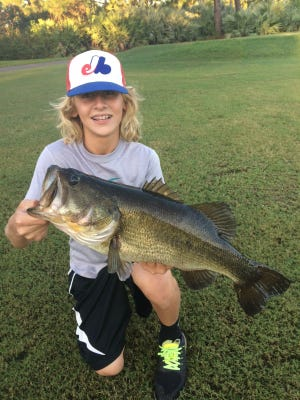 All A.J. Chew, 14, of Palm City, needed to catch and release this plump largemouth bass was his bicycle to get to tjhe pond and a topwater plug.
