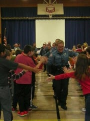 West Milford Police Officer Jill Brickman leads a train of first responders through a gauntlet of high fives from Maple Road students on Nov. 22, 2016